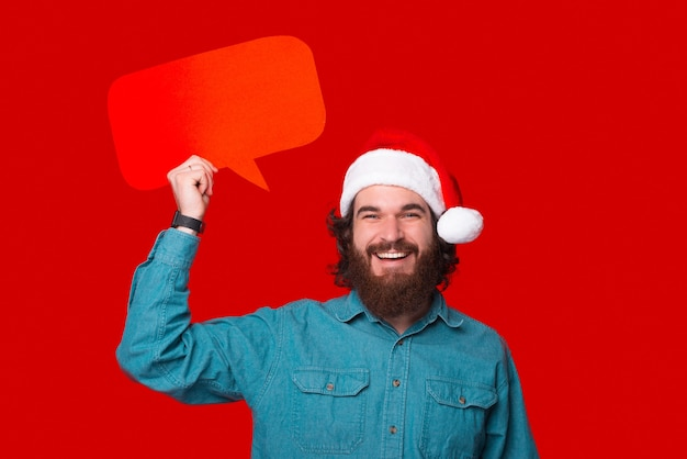 Улыбающийся человек держит красный речевой пузырь в рождественской шапке.