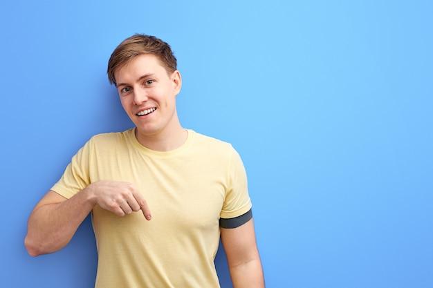 笑顔の男は人差し指を下に向けて、何か、広告の概念を示しています。人々の誠実な感情のライフスタイルの概念。コピースペースのモックアップ