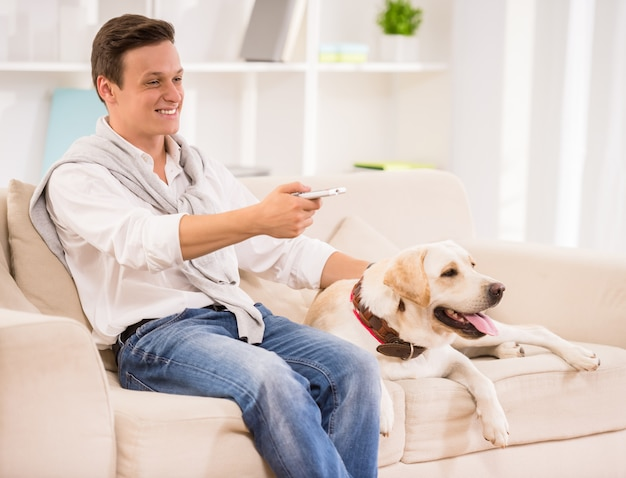 Smiling man is sitting on sofa with dog and watching tv.