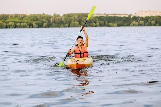 Smiling man kayaking on lake