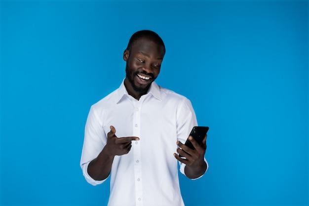 Улыбающийся человек держит телефон и смотрит на него