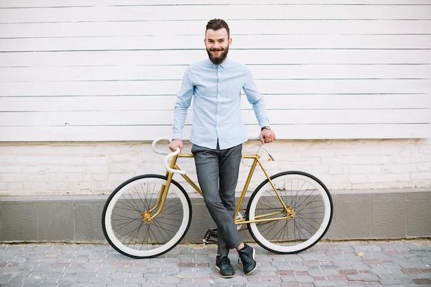 壁の近くの自転車に傾いている笑顔の男