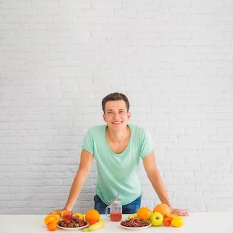 Улыбающийся человек, опираясь на стол со многими красочными фруктами