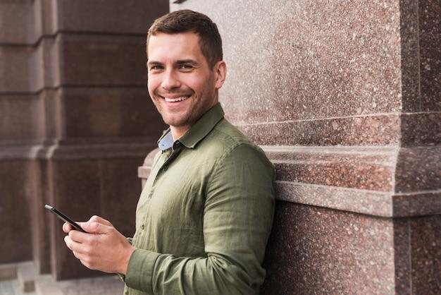 Улыбающийся человек, опираясь на стену, держа мобильный телефон и глядя на камеру