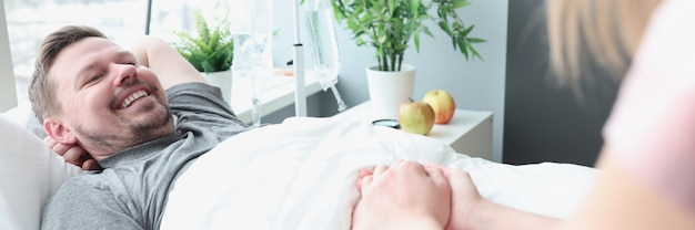 웃는 남자는 병원 침대에 누워 그의 손은 질병에 걸린 사랑하는 사람들을위한 여성 지원에 의해 개최됩니다