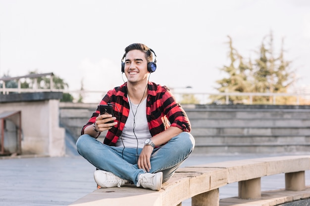 Smiling man listening to music on headphone
