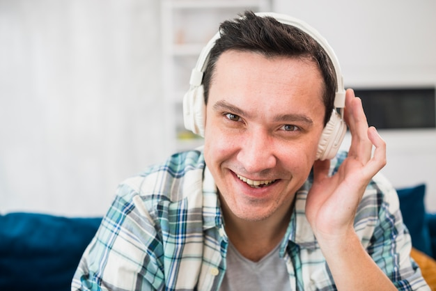Smiling man listening music in headphones on sofa