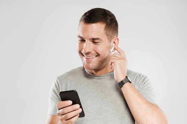 Smiling man listening music with earphones.