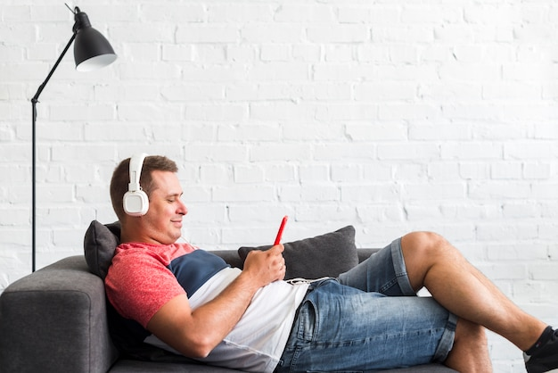 Smiling man listening music with headphone