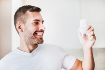 Smiling man looking at compact fluorescent light bulb
