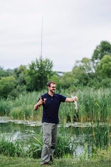 호수 근처에 갓 잡은 물고기를보고 웃는 남자