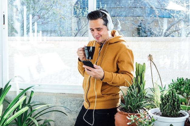Улыбающийся человек смотрит на мобильный и слушает музыку в наушниках у окна, в окружении зеленых растений и цветов