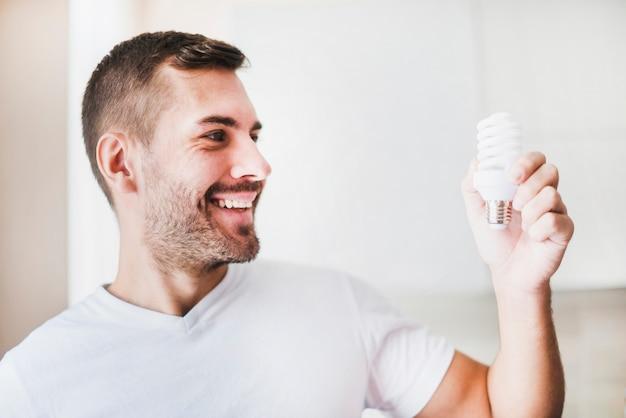 Uomo sorridente che esamina la lampadina fluorescente compatta