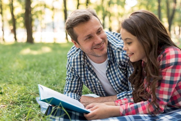Smiling man looking at his daughter reading book lying on blanket