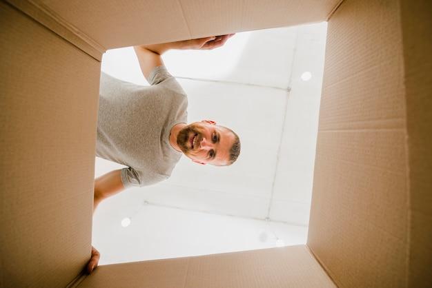 Smiling man looking inside box