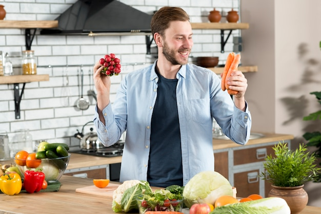 Smiling man looking at orange carrot standing behind kitchen counter