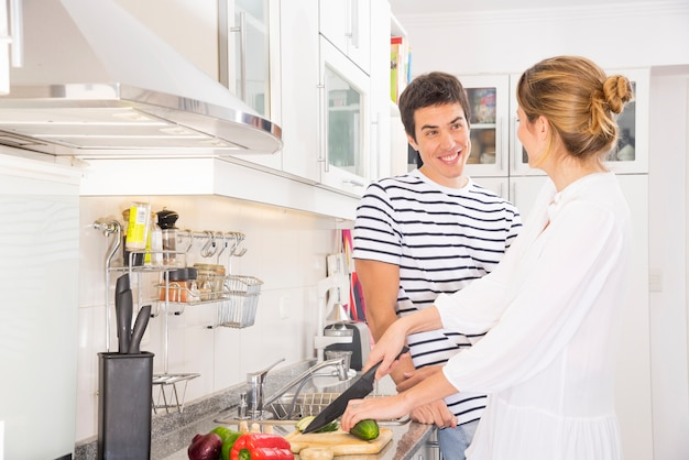 Smiling man looking at woman cutting vegetables with sharp knife