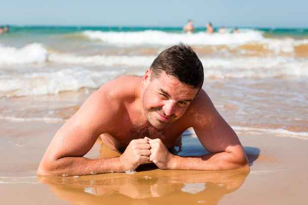 Smiling man lying on the beach on a sea background