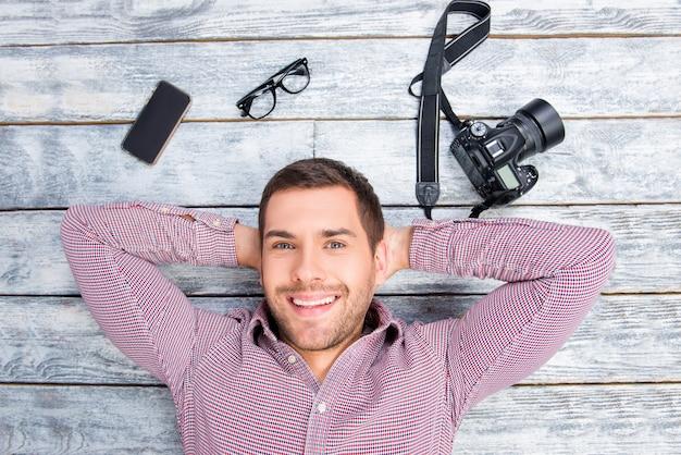 カメラで床に横たわって笑顔の男