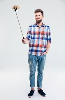 Улыбающийся человек, делающий селфи фото с палкой