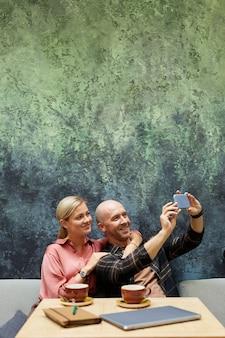커피 숍에서 자신의 시간 동안 그의 여자 친구와 함께 휴대 전화에 셀카 초상화를 만드는 웃는 남자