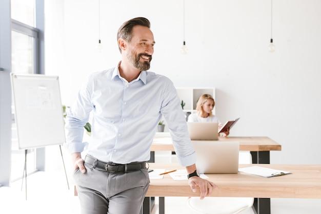 机にもたれて笑みを浮かべて男マネージャー