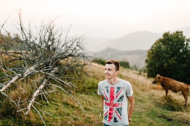 Улыбающийся мужчина, мужчины, стоящие в поле. на заднем плане корова и сухое дерево. красивые пейзажи на долину, горы и леса. летом. счастье. корова в горах. карпаты, украина.