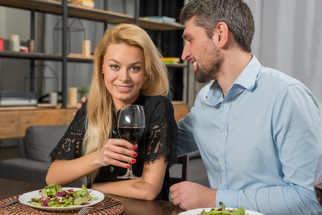 Smiling man near cheerful woman with glass at table