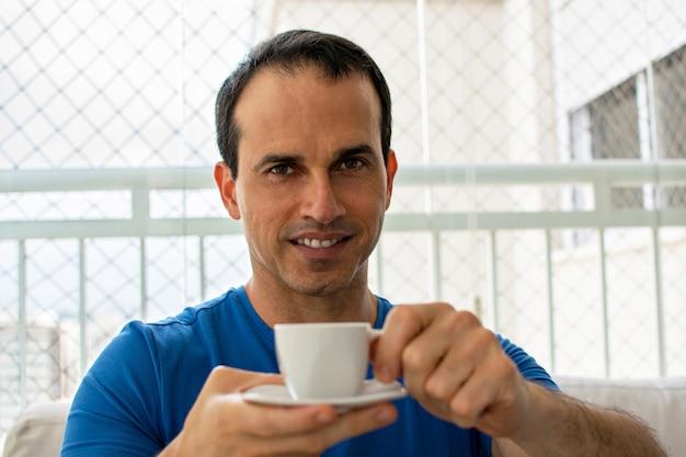 Улыбающийся человек, предлагающий чашку кофе