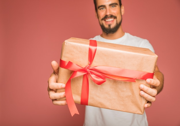 Smiling man offering gift box with red ribbon bow against colored backdrop