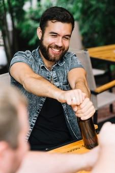 Улыбающийся человек, открыв бутылку с алкоголем, сидя в ресторане