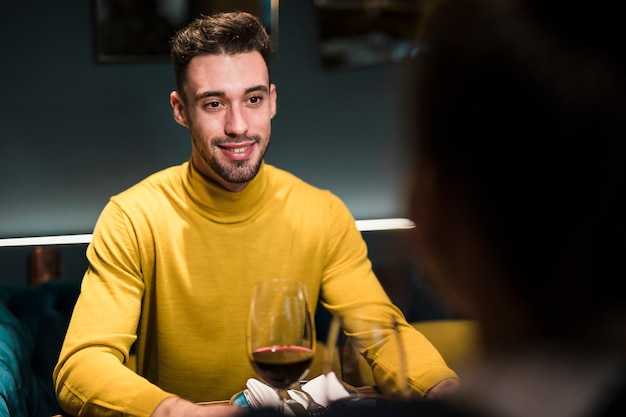 Smiling man and person sitting at table with glasses of wine