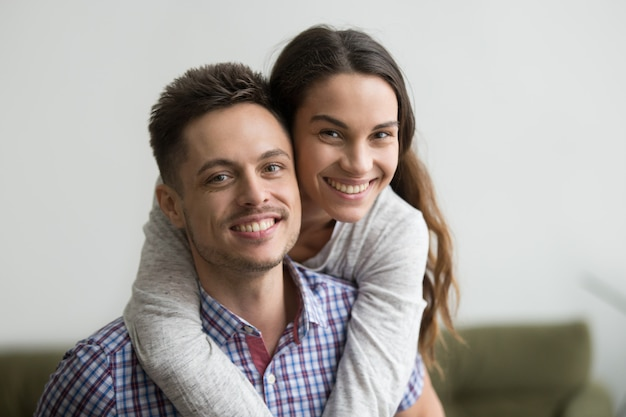 Smiling man piggyback cheerful wife looking at camera