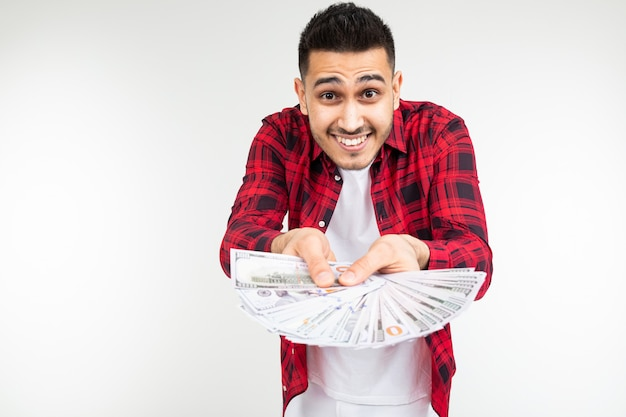 Smiling man in a plaid shirt holding out a bunch of money on a white background