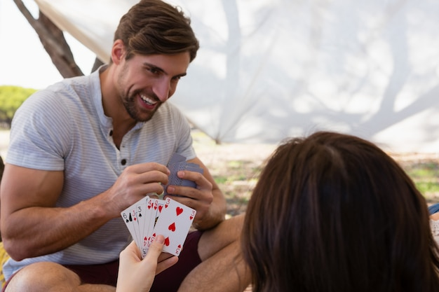 Smiling man playing cards with woman in tent