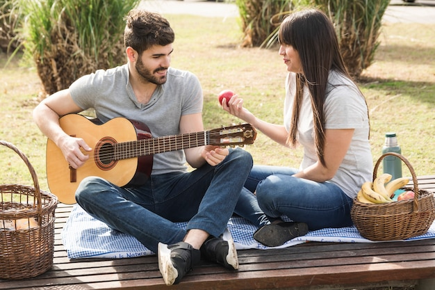 Smiling man playing guitar with his girlfriend holding red apple in hand