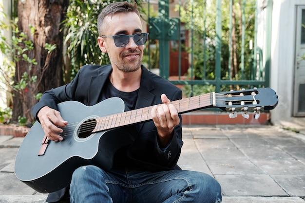 ギターを弾く男の笑みを浮かべてください。