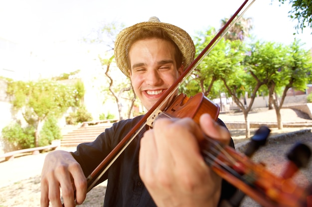 Smiling man playing a song on violin