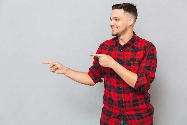 Smiling man pointing away