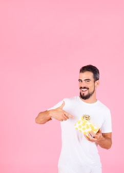 Smiling man pointing finger showing gift box with golden bow