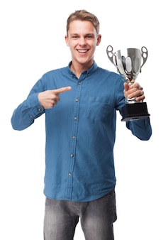 Smiling man pointing at a trophy
