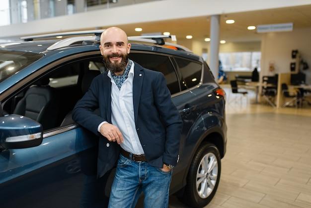 Smiling man poses at automobile in car dealership.