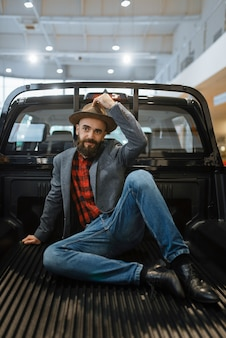 Smiling man poses in the back of new pickup truck in car dealership. customer in vehicle showroom, male person buying transport, auto dealer business