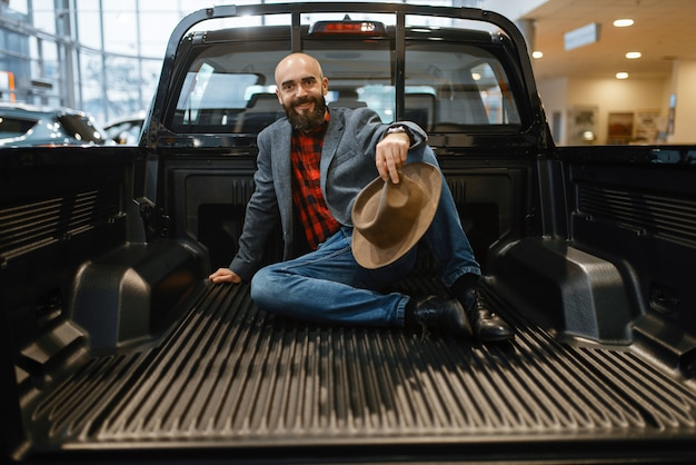 Smiling man poses in the back of new pickup truck in car dealership.