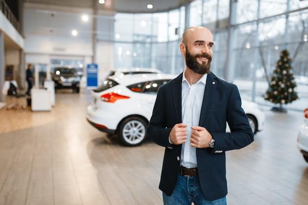 Smiling man poses in car dealership.