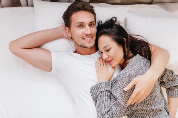 Smiling man posing in bed with wife sleeping on his chest