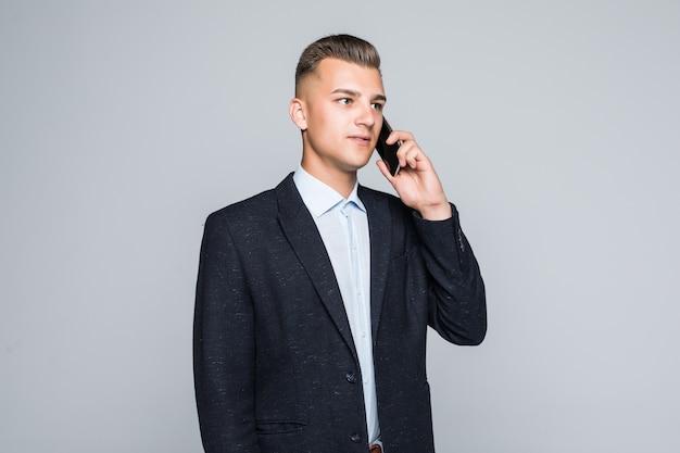 Uomo sorridente in posa con il telefono portatile vestito in giacca scura in studio isolato sul muro grigio