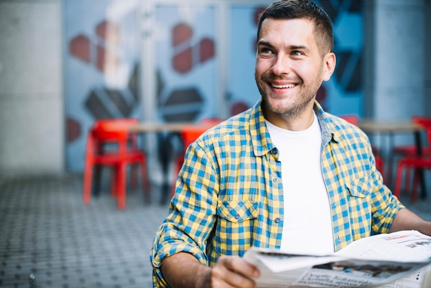Smiling man posing with newspaper