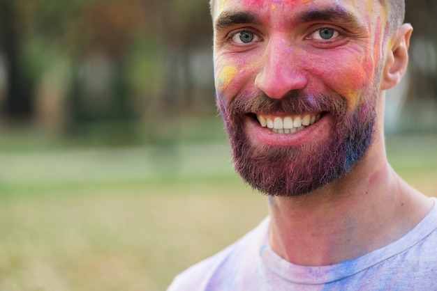 Smiling man posing with painted face at holi