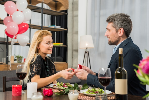 Smiling man presenting gift box to cheerful woman at table